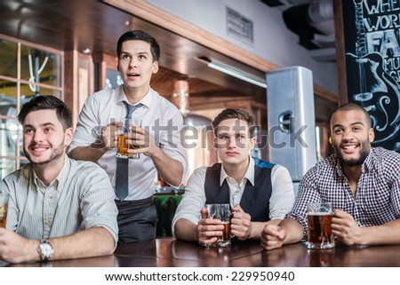 Four men fans drinking beer and watching football on TV. Four friends sitting at the table clink glasses with beer in their hands. Friends having fun together - stock photo