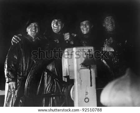 Four men in slickers standing together at the captain's wheel of a ship - stock photo
