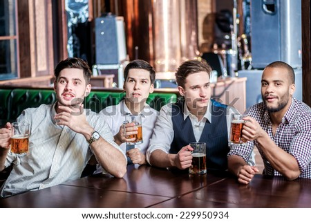 Four men team fans drinking beer and watching football on TV. Four friends sitting at the table clink glasses with beer in their hands. Friends having fun together - stock photo