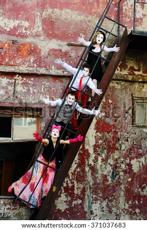 four mime on the stairs portray emotions