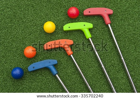 Four mini golf putters and balls of assorted colors - stock photo