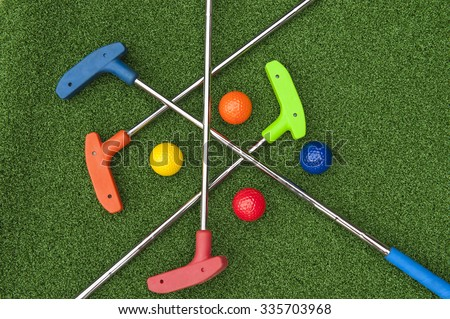Four mini golf putters and balls of assorted colors laying criss crossed on artificial grass