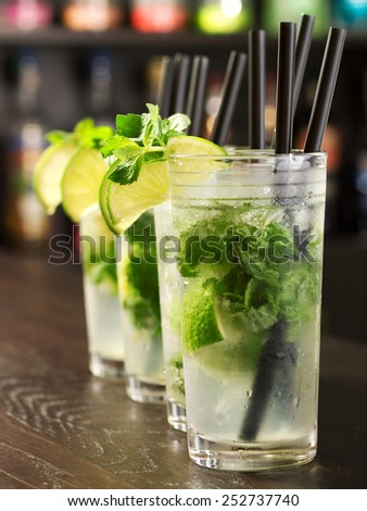 Four Mojito cocktails on a bar counter - stock photo