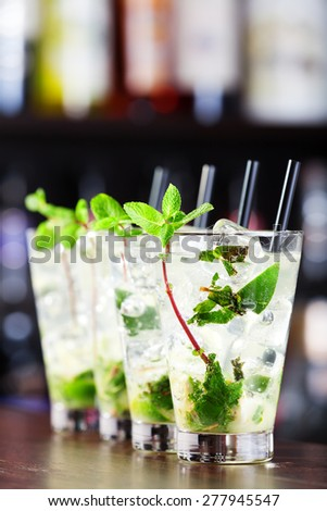 Four Mojito cocktails shot on a bar counter in a nightclub
