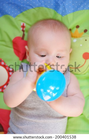 Four month old baby play with bright toy  - stock photo