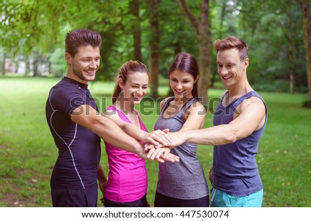 Four motivated young friends doing a stacked handshake as they stand together in a lush green park in a concept of teamwork and healthy lifestyles - stock photo