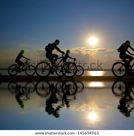 four mountain biker silhouette in sunrise with reflection in water against sun set cloudy skr Copy space for inscription