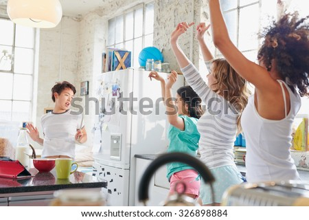Four multi racial girl friends in kitchen at home wearing pajamas dancing wildly arms in air copying moves swinging hips - stock photo