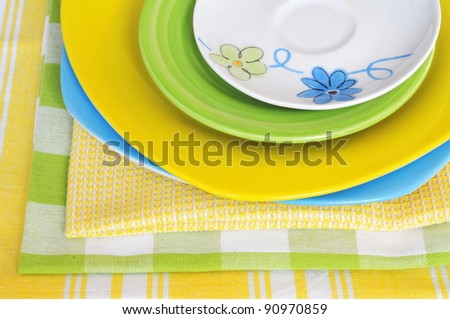 Four multicolored plates with napkins, same colors - stock photo