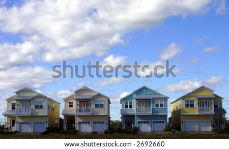 four new american dream pastel colored houses side by side - stock photo