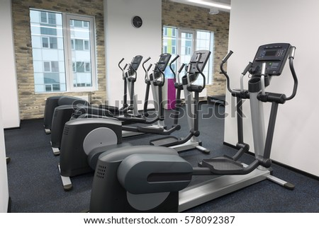 Four new elliptical trainers in modern empty hall for fitness with brick walls