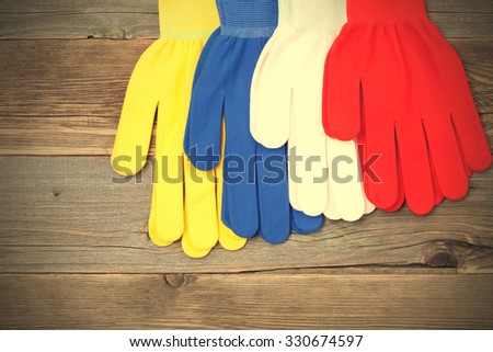 four new working colored gloves on a old wood boards. instagram image filter retro style