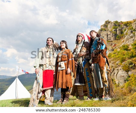 Four North American Indians of a tribe of Lakot stand at a wigwam - stock photo