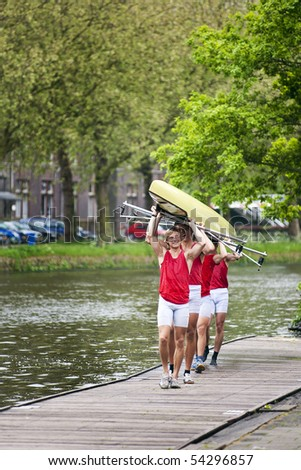 Four oarsmen carrying a rowing boat back to the boathouse after winning a race. - stock photo