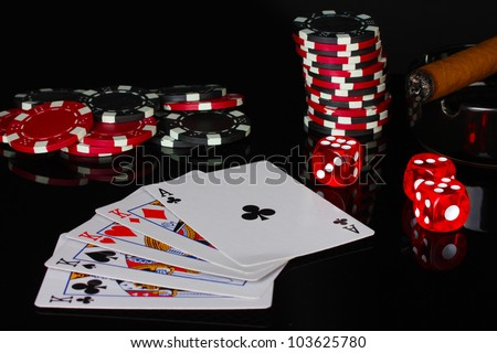 four of a kind with poker chips and dice on black background