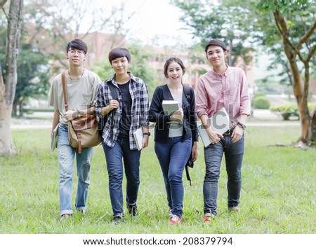 Four of the university students walking in the green field - stock photo