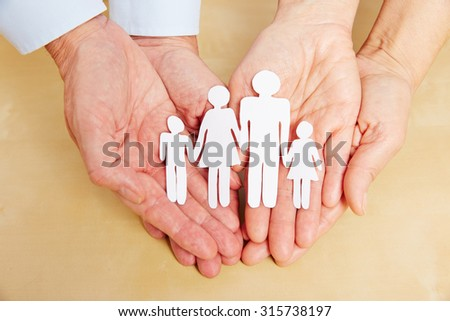 Four old hands holding a cutout paper family