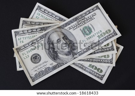 Four one hundred dollar bills isolated on black background