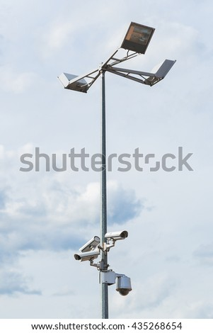 Four outside security cameras mounted on lamp post with cloudy sky background