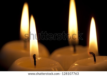 Four outstanding paraffin candles on a black background close-up