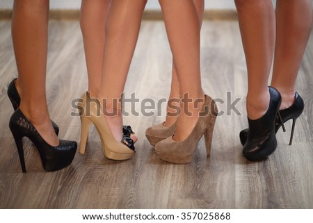 Four pair beautiful female legs with high-heeled shoes - stock photo