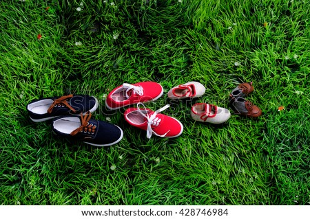 four pair of shoes in father big, mother medium and son or daughter small kid size on green grass, representing family, growth, education and togetherness concept