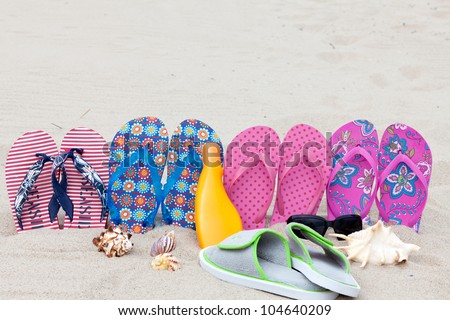 Four pairs bath slippers in a row stuck in the sand beach