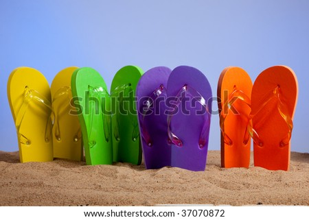 Four pairs of colorful flip-flop sandals on a beach background, studio shot - stock photo