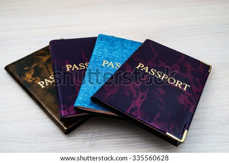 Four passports in colored covers on the table. - stock photo