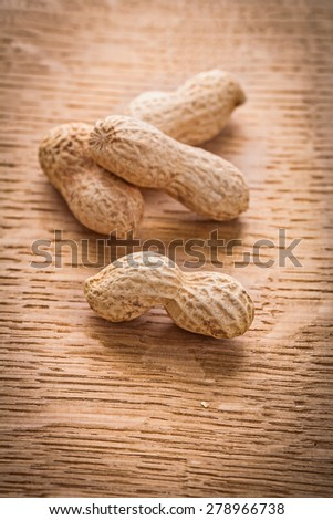 four peanuts on vintage wooden board food and drink concept  - stock photo
