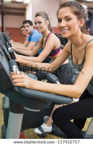 Four people enjoying time on exercise bikes in gym