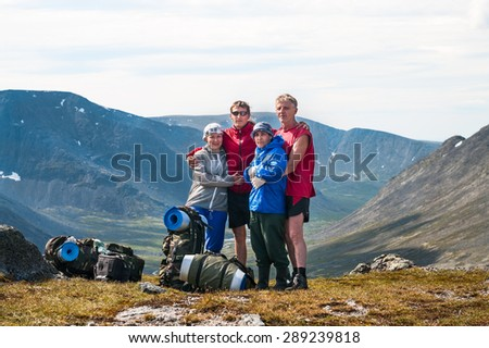 Four people family standing on the top of mountain pass together, hiking together