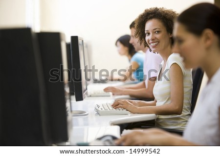 Four people in computer room typing and smiling