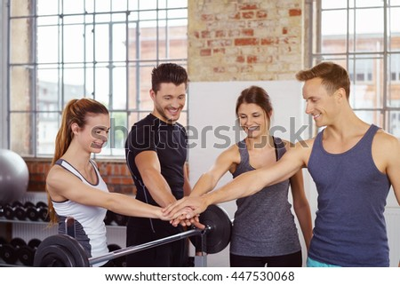Four people pledging for a successful workout by touching hands in an axis over barbell on rack at gym with large windows - stock photo