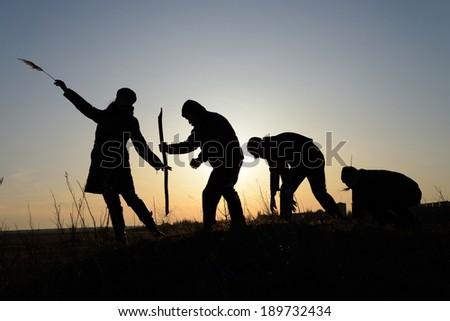 Four people silhouette against the setting sun - stock photo