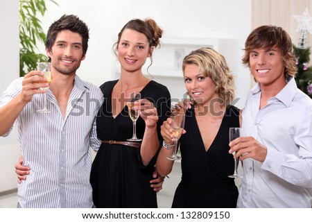 four people toasting in front of a Christmas tree - stock photo