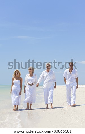 Four people, two seniors, couples or family generations, holding hands, having fun and walking on a tropical beach - stock photo
