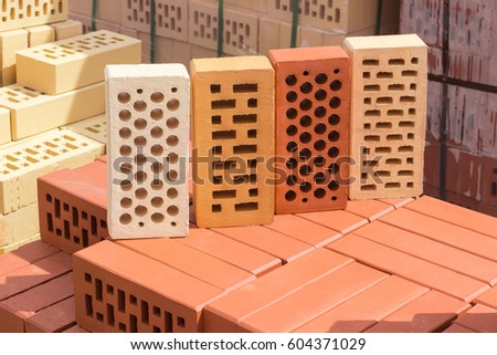 Four Perforated Bricks Of White Yellow And Red Colors With Round Rectangular Holes On