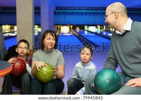 Four persons sit communicate in bowling club and hold balls, focus on mother and daughter - stock photo