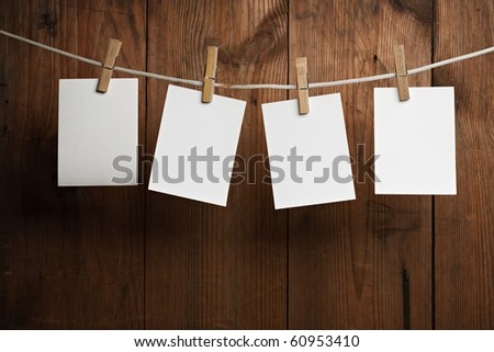 four photo paper attach to rope with clothes pins on wooden background - stock photo