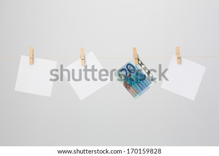 Four pieces of paper hanging on a thread. One twenty Euro note and three white notes. - stock photo