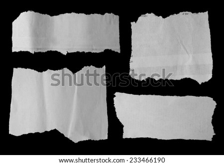 Four pieces of torn paper on black. Copy space - stock photo