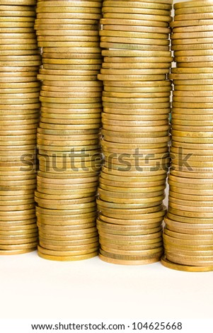 four piles of golden coins on white, mexican ten pesos coins - stock photo