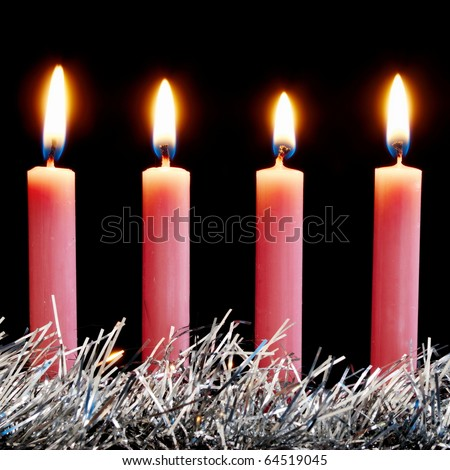 Four pink Christmas candles alight with black background - stock photo