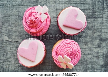 four pink cupcakes, with cream ,decorated with hearts,Valentine's day,international women's day,love. - stock photo