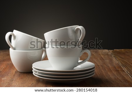 Four plain white ceramic coffee or tea cups with stacked saucers standing ready on a table in a home, cafeteria or coffee house to serve an aromatic cup of relaxing beverage - stock photo