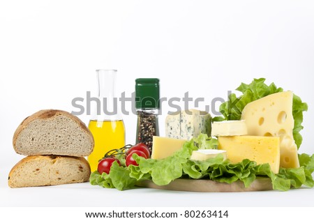 Four popular kinds of cheese, tomatoes, spices and an olive oil bottle lie on salad sheet on a white background. A shot horizontal, focus in the shot foreground. - stock photo