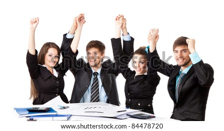 four positive smile young business people sitting at desk holding hands up over white background