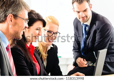 Four professionals in office in business attire looking at laptop screen working together - stock photo