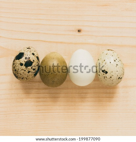 four quail eggs over wooden background - top view